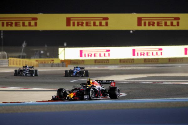 Sergio Perez, Red Bull Racing RB16B, leads Yuki Tsunoda, AlphaTauri AT02, and Esteban Ocon, Alpine A521