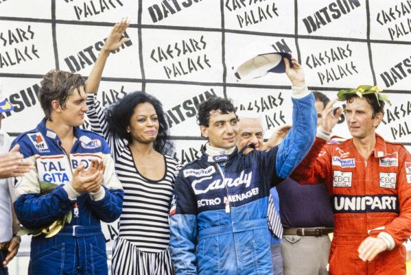 Michele Alboreto, 1st position, John Watson, 2nd position, and Eddie Cheever, 3rd position, on the podium with Diana Ross.