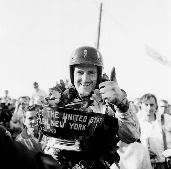 1963 United States Grand Prix.Watkins Glen, New York, USA.4-6 October 1963.Graham Hill (BRM/Owen Racing Org.) celebrates his 1st position on the podium with a thumbs-up.Ref-19776World Copyright - LAT Photographic