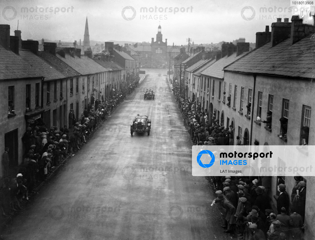 Fans line both sides of the road as Malcolm Campbell, Mercedes-Benz SS, leads Earl Howe, Mercedes-Benz SS, past them.