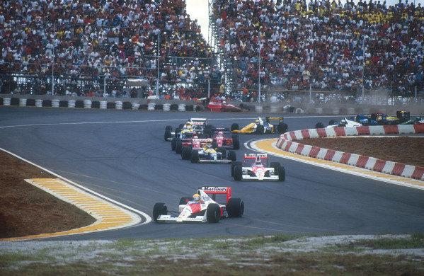 1990 Brazilian Grand Prix.Interlagos, Sao Paulo, Brazil.23-25 March 1990.Poleman Ayrton Senna easily leads teammate Gerhard Berger (both McLaren MP4/5B Honda's), Thierry Boutsen (Williams FW13B Renault), Alain Prost, Nigel Mansell (both Ferrari 641's), Riccardo Patrese (Williams FW13B Renault), Jean Alesi (Tyrrell 018 Ford) and Pierluigi Martini (Minardi M189 Ford) at the start. Behind Andrea de Cesaris retires as he crashes into the tyre barrier after colliding with Alesi.Ref-90 BRA 08.World Copyright - LAT Photographic
