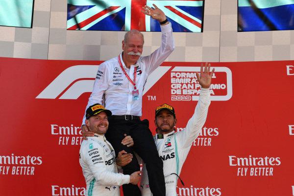 Valtteri Bottas, Mercedes AMG F1, 2nd position, and Lewis Hamilton, Mercedes AMG F1, 1st position, lift Dr Dieter Zetsche, CEO, Mercedes Benz, onto their shoulders on the podium