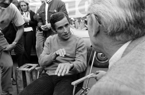 Jacky Ickx enjoys a beer in the Goodyear hospitality area after winning the race and is taking to Porsche Team Manager Fritz Huschke von Hanstein.