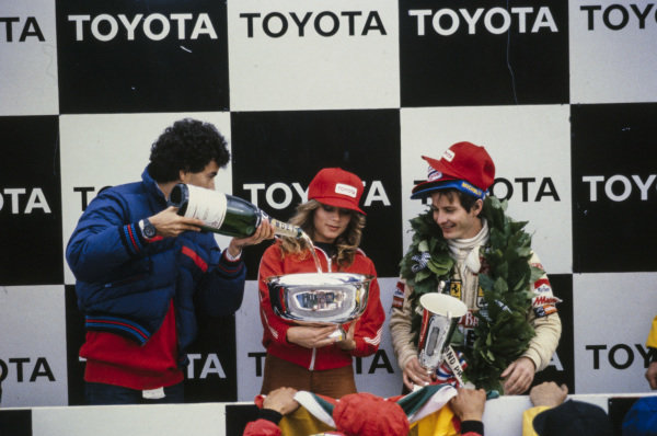Gilles Villeneuve celebrates victory on the podium. A bottle of champagne is poured into a trophy held by a woman in a Playboy jacket.