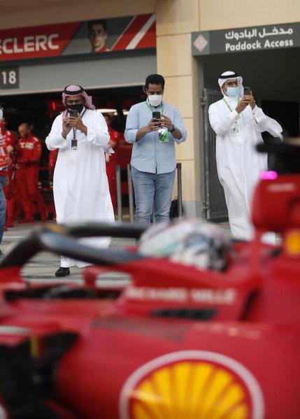 VIPs take a photo of Charles Leclerc, Ferrari SF21, in the pit lane
