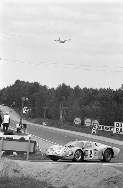 The Breguet 941, a prototype STOL transport aircraft that was ultimately not put into production, overflies the circuit, as Mark Donohue / Bruce McLaren, Shelby-American, Ford GT40 Mk4, passes.