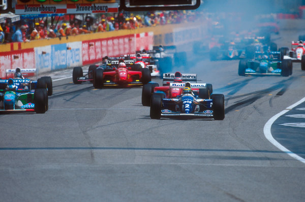 Imola, Italy.29/4-1/5 1994.Ayrton Senna (Williams FW16 Renault) leads away from pole, followed by Michael Schumacher (Benetton B194 Ford), Gerhard Berger (Ferrari 412T1) and Damon Hill (Williams FW16 Renault) at the start. Behind J.J Lehto (Benetton B194 Ford) is stalled on the grid.Ref-94 SM 05.World Copyright - LAT Photographic