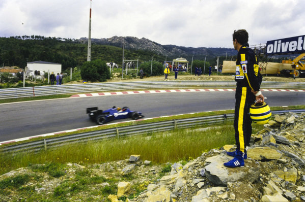 Ayrton Senna stands on rocks holding his helmet, as he watches Stefan Bellof, Tyrrell 012 Ford, drive past.
