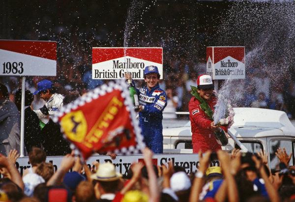 Alain Prost, Renault, sprays champagne as he celebrates victory alongside Patrick Tambay, Ferrari, 2nd and Nelson Piquet, Brabham, 3rd.