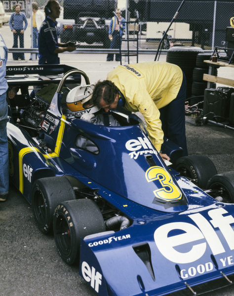 Jody Scheckter talks to an engineer whilst sat in his Tyrrell P34 Ford.