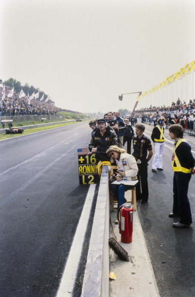 Colin Chapman and the Lotus team keep times and wait for Mario Andretti to pass the pit wall. Barbro Peterson sits close to the pit wall, beside Bob Dance.