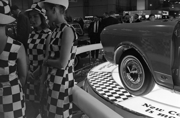 Models in chequer outfits in front of a Mk II Ford Cortina display.