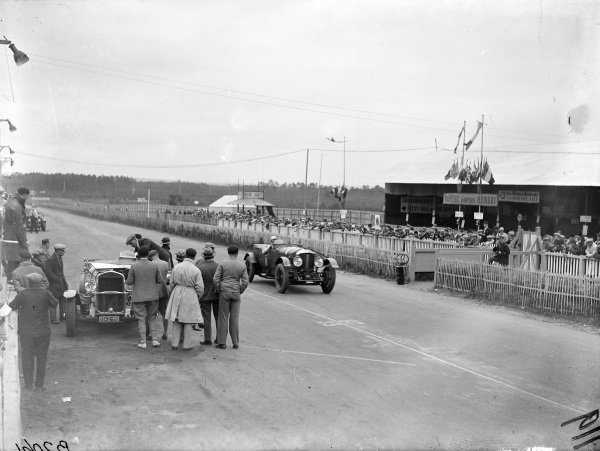 Woolf Barnato / Henry Birkin, Bentley Motors Ltd., Bentley Speed Six, passes Henri Stoffel / Robert Benoist's Chrysler Six 75, which is being worked on.