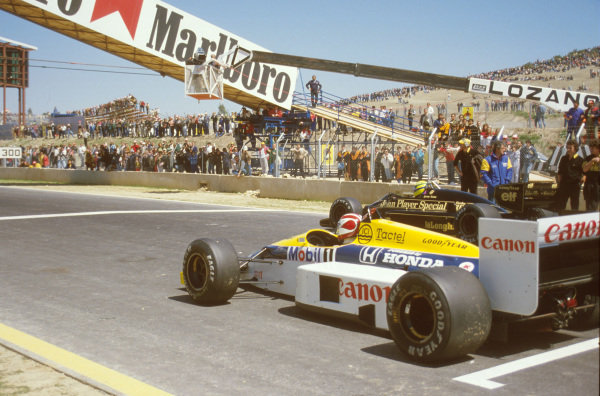 Jerez, Spain.11-13 April 1986.Ayrton Senna (Lotus 98T Renault) on pole position, with Nelson Piquet (Williams FW11 Honda) beside him on the front row about to do the parade lap.Ref-86 ESP 27.World Copyright - LAT Photographic