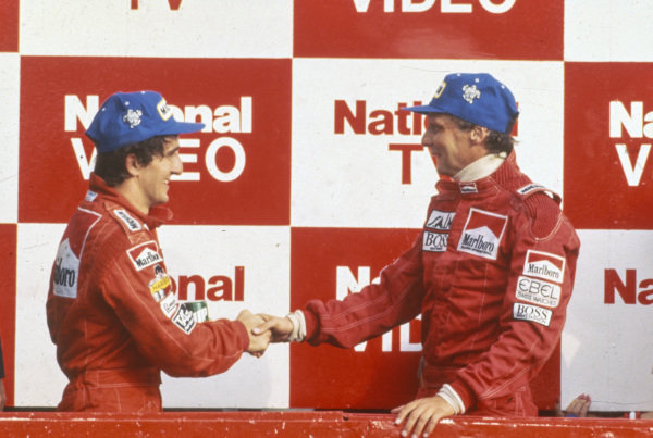 Niki Lauda, 1st position, shakes hands with teammate Alain Prost, 2nd position, on the podium.