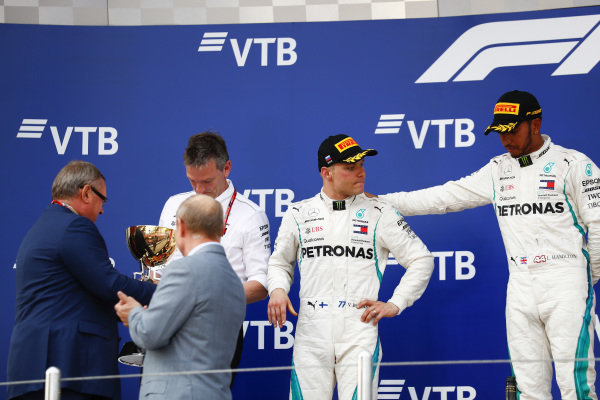 Lewis Hamilton, Mercedes AMG F1, 1st position, consoles team mate Valtteri Bottas, Mercedes AMG F1, 2nd position, on the podium as James Allison, Technical Director, Mercedes AMG, receives the Constructors trophy from Andrey Kostin, President and Chairman of the Management Board of VTB Bank