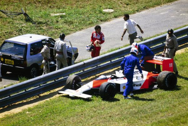 Alain Prost walks away as marshals work to recover his McLaren MP4/4 Honda.