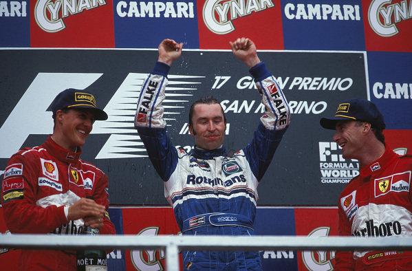 Michael Schumacher, 2nd position, Heinz-Harald Frentzen, 1st position, and Eddie Irvine, 3rd position, celebrate on the podium.