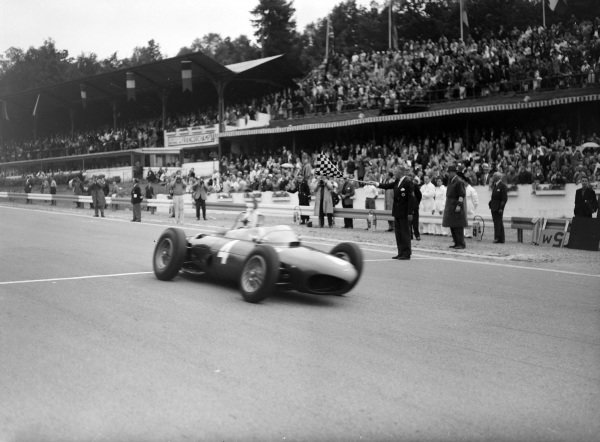 Phil Hill, Ferrari 156, crosses the line and takes the chequered flag.