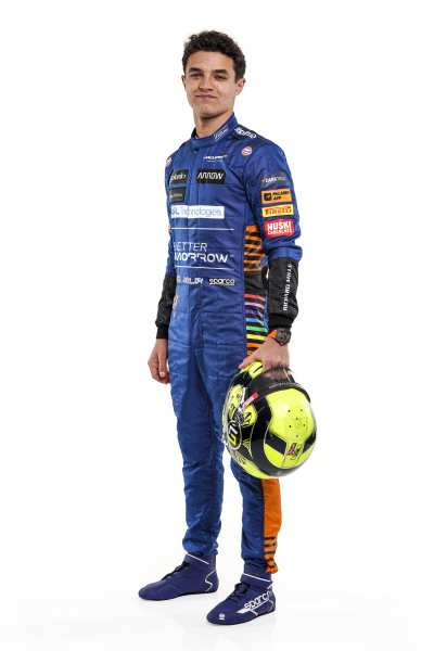 Lando Norris holding racing helmet - left hand side