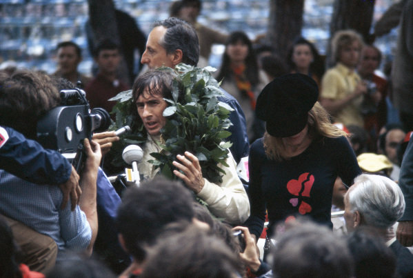 Jackie Stewart is interviewed after his victory with wife, Helen.