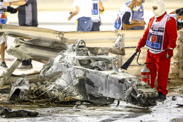 A fire marshal with wreckage after a huge crash for Romain Grosjean, Haas VF-20, on the opening lap