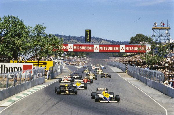 Nigel Mansell, Williams FW10 Honda, leads Ayrton Senna, Lotus 97T Renault, and Keke Rosberg, Williams FW10 Honda, on the run to the first corner.
