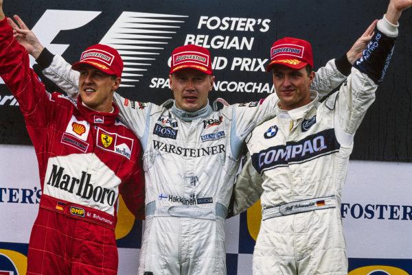 Michael Schumacher, 2nd position, Mika Häkkinen, 1st position, and Ralf Schumacher, 3rd position, on the podium.