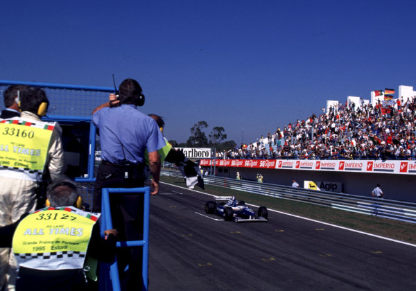 1995 Portuguese Grand Prix. Estoril, Portugal. 22-24 September 1995. David Coulthard (Williams FW17 Renault) takes the chequered flag for 1st position and his maiden Grand Prix win. World Copyright - LAT Photographic