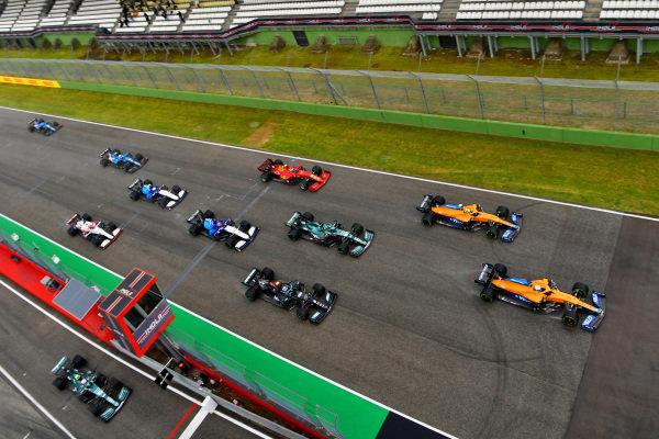Daniel Ricciardo, McLaren MCL35M, leads Lando Norris, McLaren MCL35M, Lance Stroll, Aston Martin AMR21, Valtteri Bottas, Mercedes W12, George Russell, Williams FW43B, Carlos Sainz, Ferrari SF21, and the remainder of the field at the start