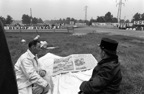 Gendarmes read the local paper with a fireman, as the cars pass at Mulsanne Corner.