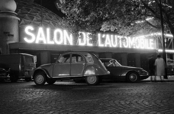 Citroen 2CV in front of the Parc des Expositions with illuminated Salon de l'Automobile sign.