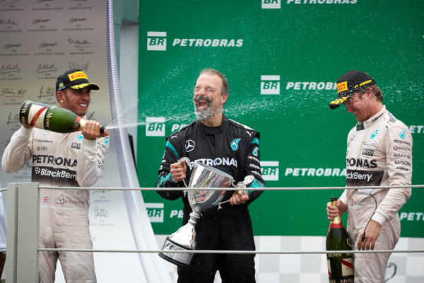 Interlagos, Sao Paulo, Brazil. Sunday 15 November 2015. Lewis Hamilton, Mercedes AMG, 2nd Position, sprays James Waddell, Composite Technician, Mercedes AMG F1, and Nico Rosberg, Mercedes AMG, 1st Position, with Champagne. World Copyright: Steve Etherington/LAT Photographic ref: Digital Image SNE13078