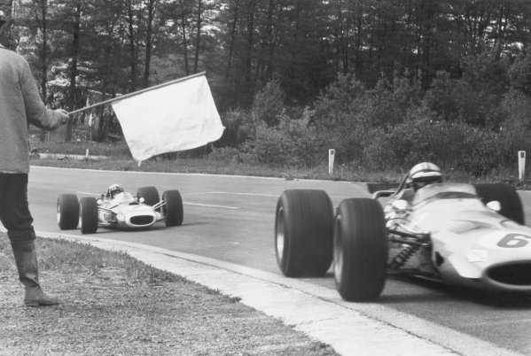 1968 Belgian Grand Prix.Spa-Francorchamps, Belgium. 9 June 1968.Denny Hulme, McLaren M7A-Ford, retired, leads Jackie Stewart, Matra MS10-Ford, 4th position, pass a flag marshal, action.World Copyright: LAT PhotographicRef: Motor b&w print