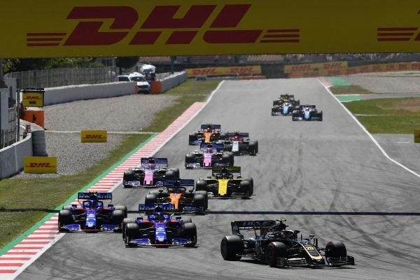Kevin Magnussen, Haas VF-19, leads Daniil Kvyat, Toro Rosso STR14, Alexander Albon, Toro Rosso STR14, Carlos Sainz Jr., McLaren MCL34, Daniel Ricciardo, Renault R.S.19, and Sergio Perez, Racing Point RP19