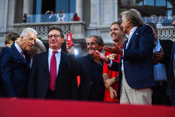 Alain Prost takes a photo on stage with Piero Lardi Ferrari, Sebastian Vettel, Ferrari and Luca di Montezemolo