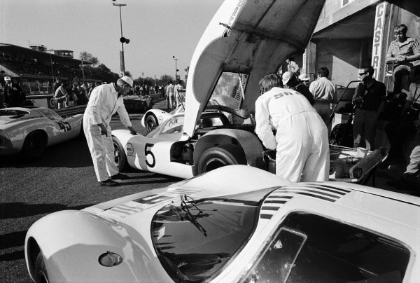 Mechanics checking on the Udo Schütz / Gerhard Mitter, Porsche System Engineering, Porsche 908 LH 027 car before the start of the race, as Ernst Kraus / Sepp Greger, Porsche 910 016, makes its way to the grid.