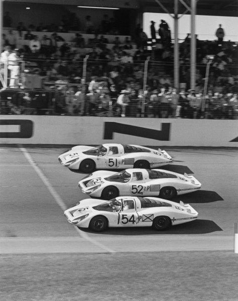 Daytona, Florida, USA. 3rd - 4th February 1968.Vic Elford/Jochen Neerpasch/Jo Siffert/Rolf Stommelen/Hans Herrmann, Porsche 907LH (#54) 1st position, crosses the finish line infront of team mates Jo Siffert/Hans Herrman/Gerhard Mitter, Porsche 907LH (#52) 2nd position and Jo Schlesser/Joe Buzzetta, Porsche 907LH (#51) 3rd position, action.World Copyright : LAT Photographic.Ref: 1864/22a-23.