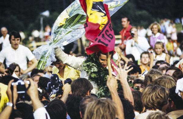 Race winner Jacky Ickx celebrates at the podium ceremony.