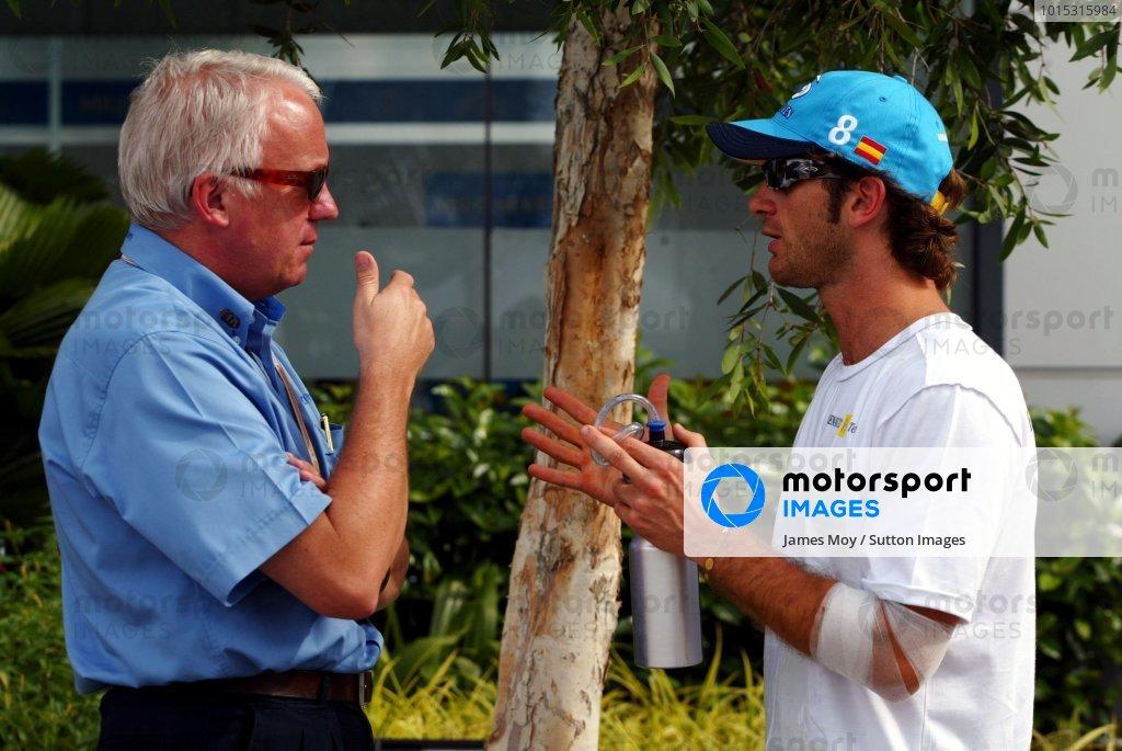 (L to R): Charlie Whiting (GBR) FIA Delegate talks with Jarno Trulli (ITA) Renault.Malaysian Grand Prix, Rd 2, Sepang, Kuala Lumpur, Malaysia, 18 March 2004.DIGITAL IMAGE