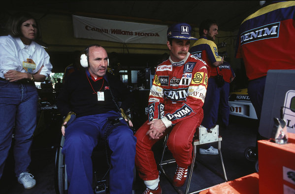Virginia and Frank Williams with Nigel Mansell watching a timing screen in the garage.