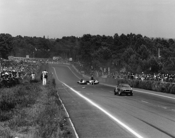 Le Mans, France. 15th - 16th June 1963 Roger Masson/Pierre Monneret (Rene Bonnet Aerodjet LM6 Renault), retired, lies upside down in th emiddle of the road as the Bruno Basini/Robert Bouharde (Rene Bonnet Aerodjet LM6 Renault), Not Classified, approaches, action. World Copyright: LAT Photographic Ref:  19325.