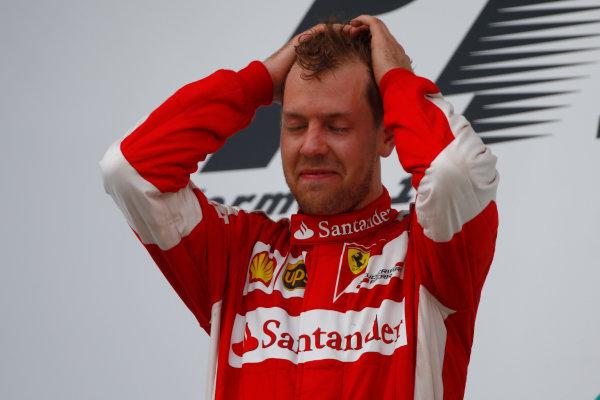 Sepang International Circuit, Sepang, Kuala Lumpur, Malaysia. Sunday 29 March 2015. Sebastian Vettel, Ferrari, 1st Position, celebrates on the podium. World Copyright: Andrew Hone/LAT Photographic. ref: Digital Image _ONZ0437