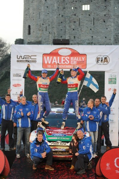 Jari-Matti Latvala (FIN) and Miikka Anttila (FIN) celebrate victory, with the Ford World Rally Team, on the podium in Cardiff Castle.