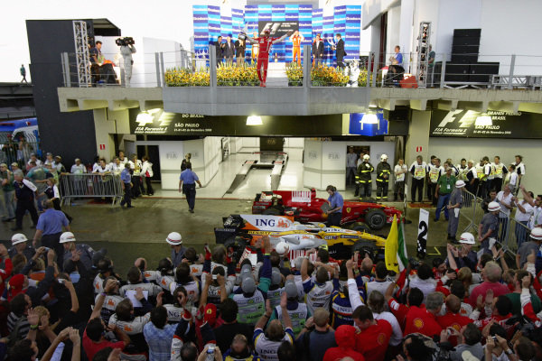 The teams gather to watch the podium ceremony where winner Felipe Massa holds up his trophy in celebration.