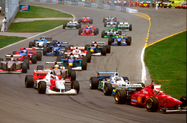 Montreal, Quebec, Canada.14-16 June 1996.Eddie Irvine (Ferrari F310) is followed by Gerhard Berger (Benetton B196 Renault) and Mika Hakkinen (McLaren MP4/11 Mercedes) at the start.Ref-96 CAN 01.World Copyright - LAT Photographic