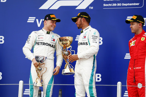 Valtteri Bottas, Mercedes AMG F1, 2nd position, and Lewis Hamilton, Mercedes AMG F1, 1st position, talk on the podium alongside Sebastian Vettel, Ferrari, 3rd position