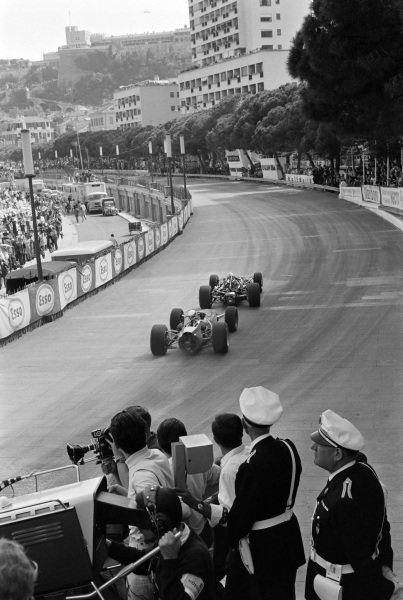 Denny Hulme, Brabham BT20 Repco, and Jackie Stewart, BRM P261, drift out of Tabac corner.
