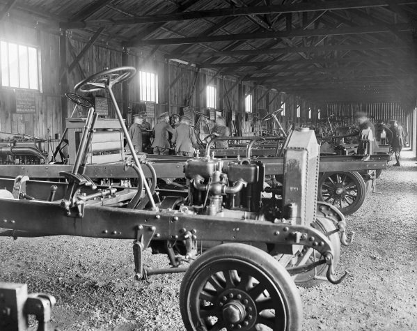 A row of stripped lorry chassis, each with a descriptive board on the wall behind it, used for instructing drivers and mechanics, at the Army Service Corps Motor Transport Depot in Isleworth.