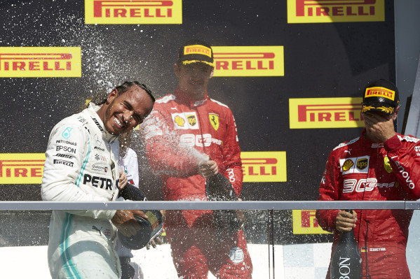 Lewis Hamilton, Mercedes AMG F1, 1st position, Charles Leclerc, Ferrari, 3rd position,, and Sebastian Vettel, Ferrari, 2nd position, with Champagne on the podium